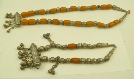 TWO DECORATIVE NECKLACES, possibly Bedouin, white metal and bead, possibly amber