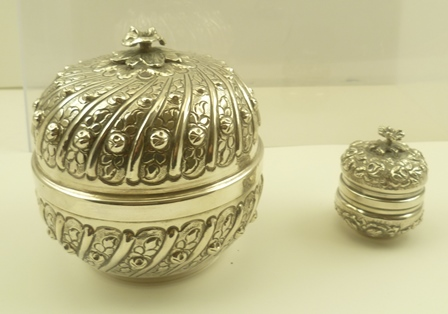 TWO EASTERN WHITE METAL BOXES with domed covers, having cast floral finials and gilded interiors, overall embossed floral decoration, both stamped .900, tallest 12cm