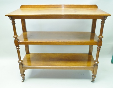 A LATE 19TH CENTURY OAK FINISHED THREE TIER BUFFET with turned and blocked fore supports, plain rear, with white ceramic castors, 110cm to height of first tier, 122cm wide