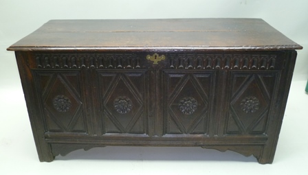 AN 18TH/19TH CENTURY OAK COFFER with plain plank top, over carved four panel front, having vacant interior, 68cm high x 137cm wide