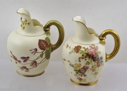 TWO ROYAL WORCESTER PORCELAIN VICTORIAN CARAFE JUGS, white glazed, each with polychrome decoration and gilt handles, model 1094, date codes 1893 & 1887, 14cm high