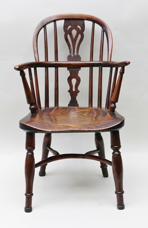 AN EARLY 19TH CENTURY POSSIBLY WELSH BORDERS, CHILDS ARMCHAIR, with double comb back, elm seat and yew wood back, supported on four turned splay legs united by a crinoline stretcher, 67cm high