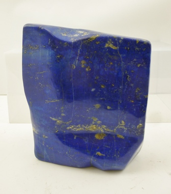 A LARGE POLISHED BLOCK SPECIMEN OF LAPIS LAZULI, whose blue colour is pigment known as ultramarine, from the Latin ultramarinus (beyond the sea), as it came into Europe to be used as an Artists pigment from the mines of Afghanistan via Italian traders in the 14th and 15th centuries, 19.5cm high, weight approximately 5,820g.