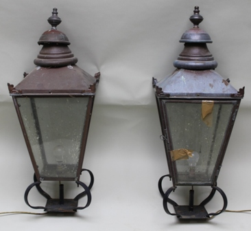 A PAIR OF VICTORIAN DESIGN COPPER FINISHED GATE PILLAR LAMPS in the style of street lamp hoods, of tapering square form with turned finials, glazed in the round, on wrought iron bases, 95cm high x 36cm square