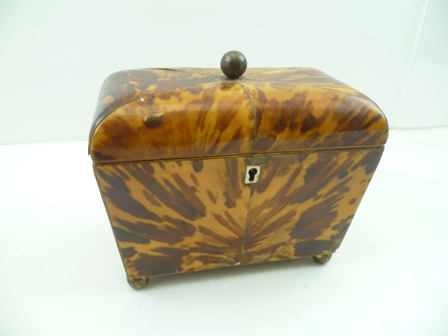 A 19TH CENTURY TORTOISESHELL TEA CADDY, the hinged cover with brass ball handle, opening to reveal twin sections, raised on ball feet, 18cm wide