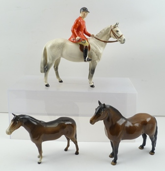 A BESWICK HUNTSMAN on a dapple grey horse, model 1501, gloss finish, 21cm high, together with a DARTMOOR PONY and one other BAY HORSE (3)