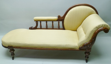 A LATE VICTORIAN SHOW FRAMED SINGLE END CHAISE LONGUE, upholstered in patterned gold fabric, having carved scroll arm, on turned supports with castors