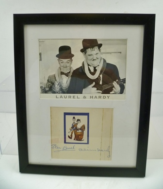 STAN LAUREL AND OLIVER HARDY AUTOGRAPHS, mounted together with an image of the pair, within a single ebonised frame, overall size including frame 28.5cm x 23cm