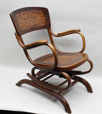 A THONET BENTWOOD ROCKING CHAIR, raised on sprung frame, having decorative back support panel and seat, bears printed manufacturers label