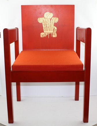 A PRINCE OF WALES INVESTITURE CHAIR, designed by Lord Snowdon, red beech veneer with gold fleur de lys crest, Welsh tweed upholstered seat pad, designed by Lord Snowdon for Remploy 1969, 78cm high, in original card box