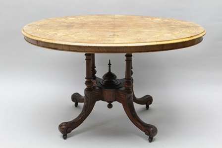 A VICTORIAN WALNUT VENEER LOO TABLE, the quarter top with bird marquetry inlay, the oval tilt-top on a base of four ring turned columns with outswept scroll toe supports, 120cm