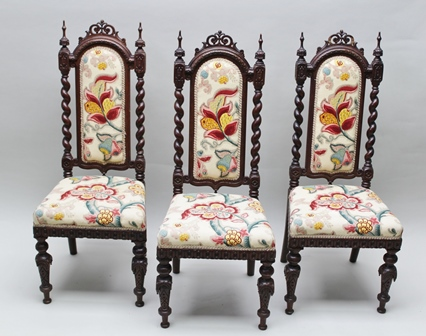 THREE LATE VICTORIAN CARVED SHOW FRAMED HALL OR SIDE CHAIRS, in the Gothic taste, having pierced crests, the backs with barley twists flanking an upholstered pad back, upholstered seats, on carved forelegs, upholstered in Nina Campbell fabric of crewel work design