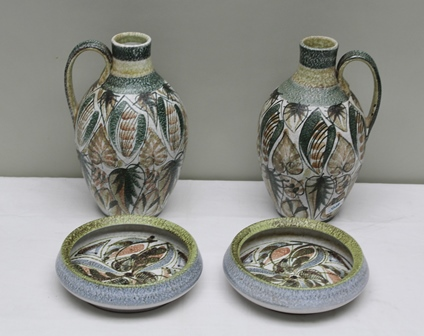 A PAIR OF GLYN COLLEDGE, FOR BOURNE GLAZED STONEWARE EWERS, with strapwork handles, stylised leaf decoration, 31cm high, together with a PAIR OF MATCHING BOWLS, 21cm diameter