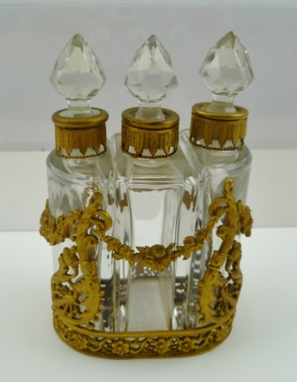 A FRENCH GILT METAL MOUNTED SCENT BOTTLE HOLDER, fitted three bottles with stoppers