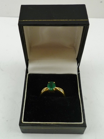 AN EMERALD RING, with diamonds set to the shanks, on an 18ct gold band, size M
