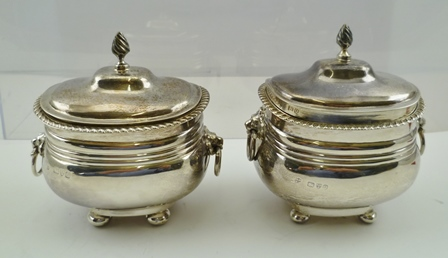 NATHAN & HAYES A MATCHED PAIR OF GEORGIAN STYLE SILVER CUSHION SHAPE CADDIES/SUGARS, each having a hinged lid with flame finial, gadroon rim, twin lion mask ring handles, raised on four bun feet, Chester 1899 and 1904, 356g