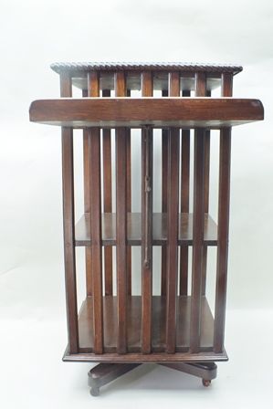 AN EARLY 20TH CENTURY OAK FINISHED TALL REVOLVING BOOKCASE with folding reeded slope side, having plain top with ropework edge, with traditional slat and shelved base supported on a four point stand with castors below, 104cm high