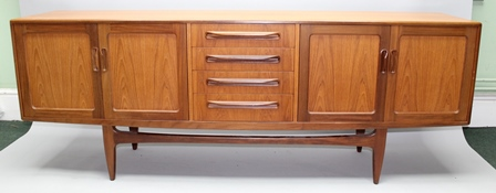 A RETRO DESIGN RED LABEL G-PLAN EXTRA LONG AND LOW SIDEBOARD having four central drawers flanked by two pairs of plain panelled doors, supported on plain tapering legs, 214cm wide