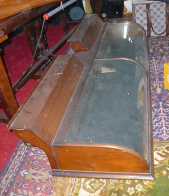 AN EDWARDIAN MAHOGANY SHOP COUNTER DISPLAY CASE with arched glass front panels and raised shelf back, accessed via the back mirrored panels, 153cm wide