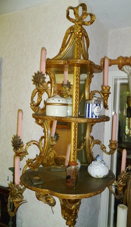 A PAIR OF GILT GESSO TRIPLE MIRROR BACKED CORNER DISPLAY UNITS of scrolling Rococo form, each fitted six candle sconces, with tied ribbon crests