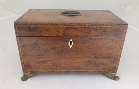 AN EARLY 19TH CENTURY YEW-WOOD TEA CADDY with metal fittings, opening to reveal twin caddy boxes with lids, decorative ring mask handles, raised on metal paw feet