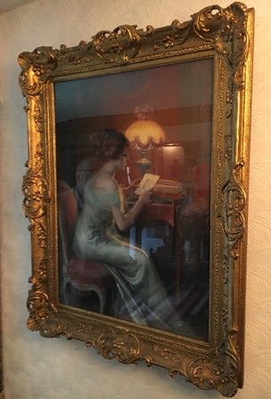 EUROPEAN SCHOOL - PASTEL DRAWING of an Edwardian lady at her desk studying an image in the light of her lamp, indistinctly signed, 70cm x 50cm, in ornate gilt frame