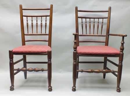 A WELL-MADE REPRODUCTION SET OF SIX COUNTRY SPINDLE BACK OAK CHAIRS with turned forelegs with stretcher between comprising four singles and two carvers, trellis pattern upholstered drop-in seat pads