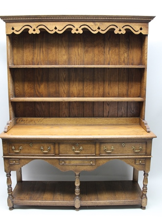 A WELL-MADE REPRODUCTION DRESSER with dentil cornice over twin shelved plate rack back, supported on a base having plain rectangular top with three in-line drawers over three slender secondary drawers, having turned and blocked forelegs, plain rear,united by a planked pot under tier, approx 195cm high