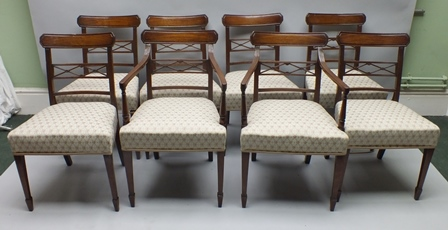 A SET OF EIGHT LATE REGENCY MAHOGANY DINING CHAIRS, having solid crest rail with double X formed central slat and plain reeded lower slat, trellis patterned upholstered overstuffed seat pads, on plain square tapering forelegs with spade feet, comprising six singles and two carvers, 82cm high