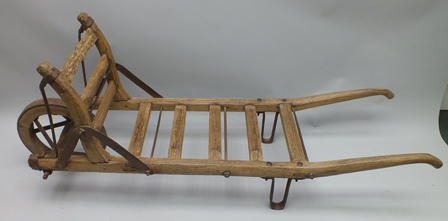 A 19TH CENTURY METAL FRAMED BREWERS BARREL CADDY having slatted wood frame and single iron bound wheel, approx 190cm long