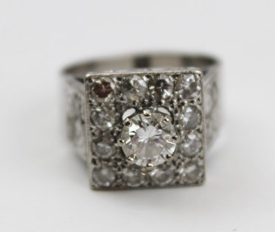 A DIAMOND RING, having central brilliant cut stone on a square field, diamond set, with diamonds to the shanks, 18ct white gold set, size L 1/2