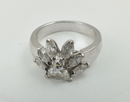 A DIAMOND SET RING of individually commisioned Mayan design, a trillion stone with a fan of six marquise shape stones, brilliant cut, mounted in 18ct white gold, ring size L (in ring box)