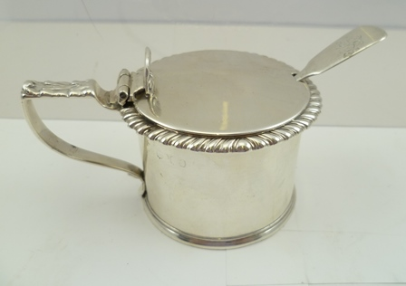 BARNARD FAMILY A VICTORIAN SILVER MUSTARD (with monogrammed spoon), having circular hinged lid, gadrooned rim, decorative handle, plain body with a blue glass liner, London 1830