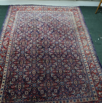 A WOVEN WOOLLEN PERSIAN MAHAL with blue and red ground, having busy central field, flanked by multi-guard border, 234cm x 325cm