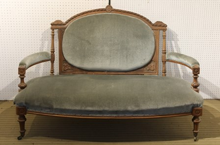 AN EDWARDIAN CARVED SHOW-WOOD OPEN ARM TWO SEATER SOFA, with upholstered oval back pad, arm pads and seat, raised on turned and fluted fore supports with brass castors