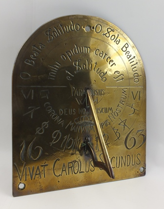A 19TH CENTURY BRASS SUNDIAL, wall mounting arched plate, engraved with text and calibrations, bears the date 1663, and the inscription ..... Vivat Carolus Secundus, 30.5cm high x 25.5cm wide (the Vendors family history is that this item was removed from the stable block at Witley Court)