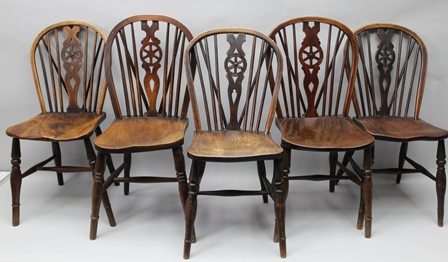 A MATCHED SET OF FIVE PROVINCIAL WHEELBACK  SINGLE CHAIRS circa 1900, with shaped elm seats, on ring turned supports with H stretchers