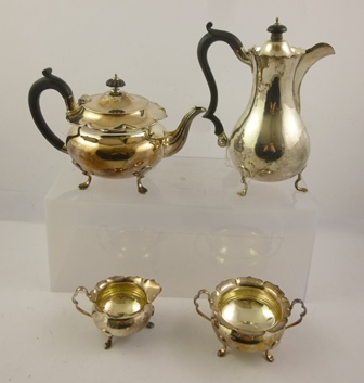 NATHAN & HAYES AN EDWARDIAN FOUR PIECE SILVER TEASET comprising; teapot, hot water, sugar and milk, each piece with wavy cut rim and baluster shaped body, raised on duck pad feet, Chester 1903, 1307g