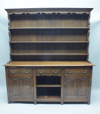 AN EARLY 20TH CENTURY OAK DRESSER having triple shelved plate rack back, over three in-line drawers, open central section, flanked by two panelled cupboard doors, on block feet, 203cm x 181cm wide