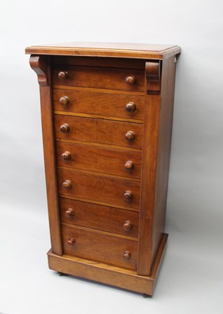 A 19TH CENTURY MAHOGANY WELLINGTON CHEST, fitted seven drawers, raised on box base with castors, 124cm high x 57cm wide