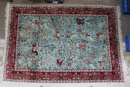 A 20TH CENTURY PERSIAN RUG having central blue field with all over hunting scene, archers on horseback amidst stylised trees, within a deep red deep border, fringed, outer border bears signature, 176cm x 250cm