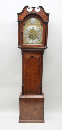 GRINDAL, DUMFRIES AN OAK LONGCASE CLOCK, the hood with broken swan neck pediment, column mounted, the case with quarter columns and box base, the eight day striking movement with arched dial, cast spandrels, secondary dial and date aperture, silvered chapter ring with Roman hours and Arabic minutes, 207cm high