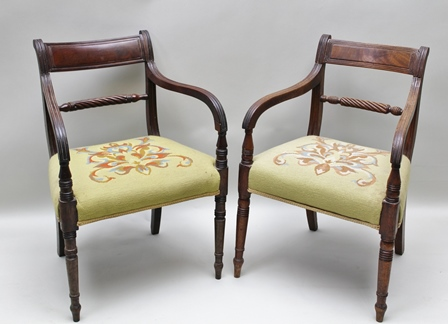 A MATCHED SET OF TEN REGENCY MAHOGANY DINING CHAIRS, of rope twist form, comprising two open arm carvers and eight singles, raised on ring turned supports, woolwork seats