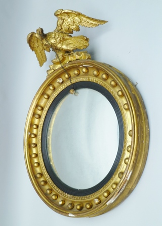 A 19TH CENTURY GILT FRAMED CONVEX WALL MIRROR, the ball mounted frame with an eagle mount, the eagle bears a chain and ball within its beak, mirror plate 36cm diameter