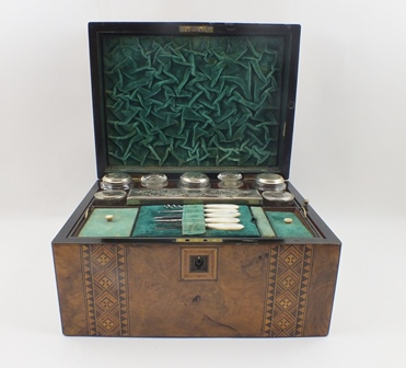 A 19TH CENTURY WALNUT VENEERED DRESSING BOX with Tunbridge style inlay, opens to reveal a fitted interior, with silver plated lidded appointments, 30cm wide