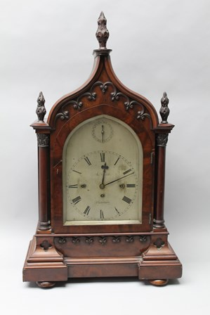J. HOWLETT OF CHELTENHAM A 19TH CENTURY GOTHIC REVIVAL MAHOGANY CASED BRACKET CLOCK, the case with carved acanthus leaf finials, tracery to the case over the arched glass door flanked by columns on inverted breakfront base, on bun feet, the silvered dial with chime/silent indicator over dial with Roman numerals, engraved J. Howlett Cheltenham, fitted 8-day triple fusee musical chiming movement on the quarters, 81cm high x 48cm wide, complete with wall mounting bracket