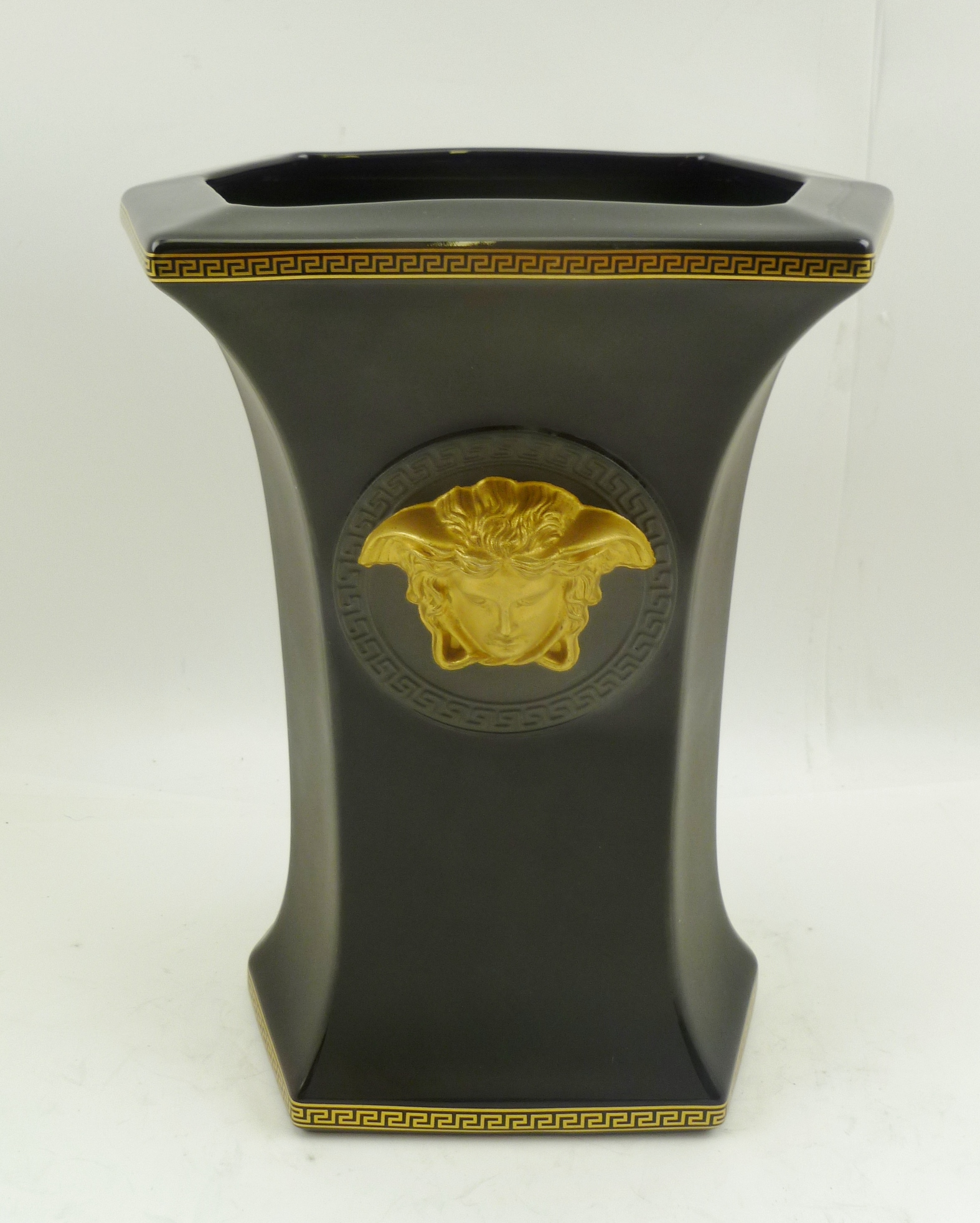 A ROSENTHAL VERSACE CERAMIC VASE, of waisted hexagonal form, black ground, with Greek key borders, classical mask gilded to one side, matt pewter to the verso, factory stamps to base, 23cm high