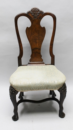 AN EARLY 18TH CENTURY CONTINENTAL WALNUT SINGLE CHAIR, vase splat back with carved crest, shaped seat over stuffed and upholstered, raised on carved cabriole front supports with shaped stretchers