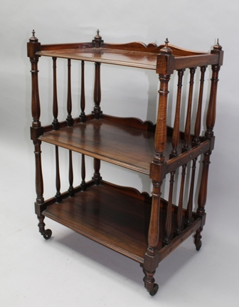 A 19TH CENTURY MAHOGANY THREE-TIER WHATNOT, raised on turned supports, a shaped low gallery back, on castors, 66cm wide