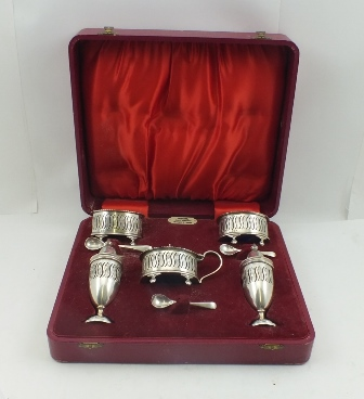 ELLIS & CO. A CASED SILVER CONDIMENT SET of Georgian design, comprising a pair of salts, pierced and chased decoration, raised on ball and claw feet, a hinged lidded mustard pot, a pair of urn form pepperettes, with blue glass liners, together withtwo matched silver condiment spoons, in a red silk and velvet lined case, with label Ogdens, Court Jewellers Harrogate & London, Birmingham 1957